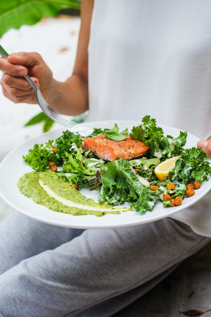 Baked Salmon with Pumpkin Seed Pesto, Creamy Kale Salad & Chickpea Croutons on a plate