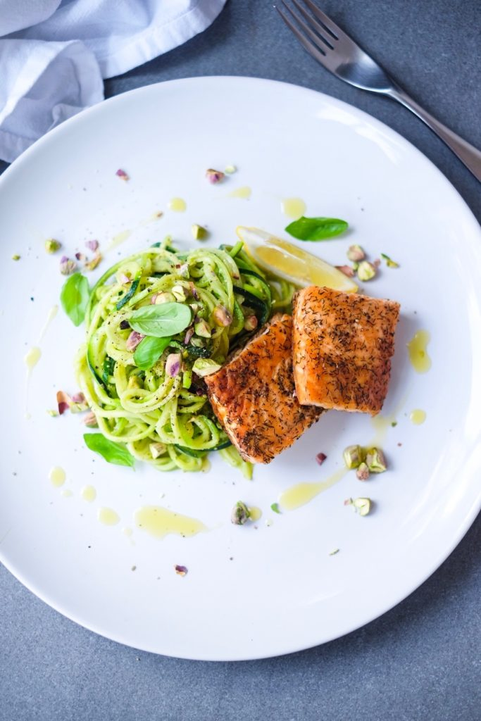 Baked Salmon with Pesto Zoodles & Pistachios on a plate